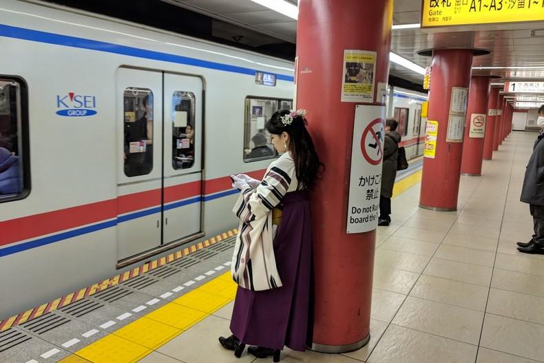 Une jeune Japonaise en costume traditionnelle attend le métro adossée à un pylone