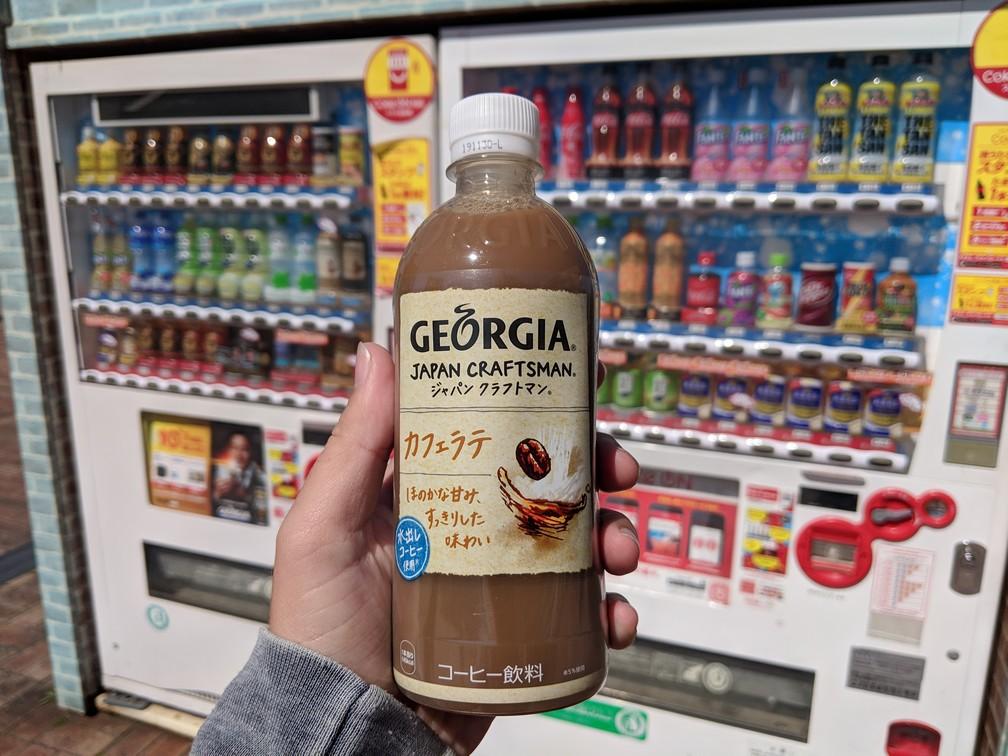Sylvain tient une bouteille de café latte froid devant un distributeur de boissons japonais