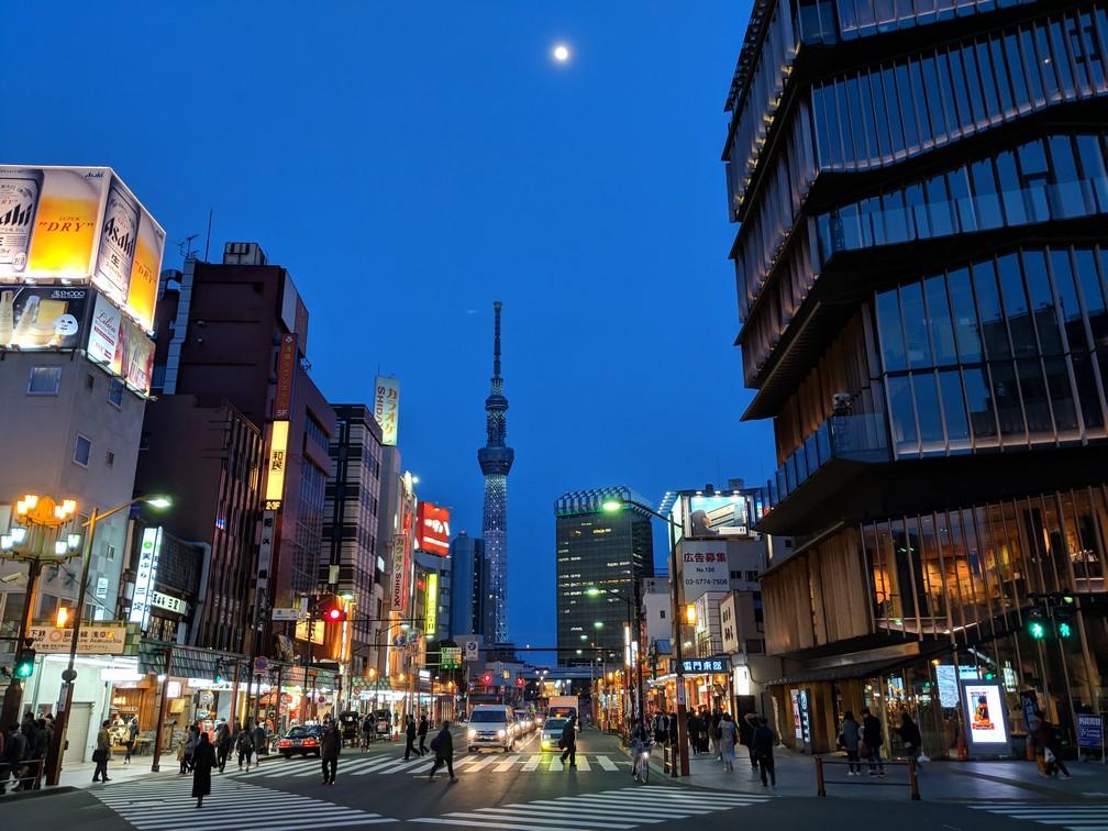 Un carrefour d'Asakusa de nuit, la Sky Tower au fond avec la lune au dessus