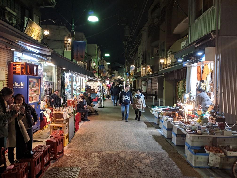 Une rue commercante éclairée par ses petites boutiques et fréquentée par quelques passants