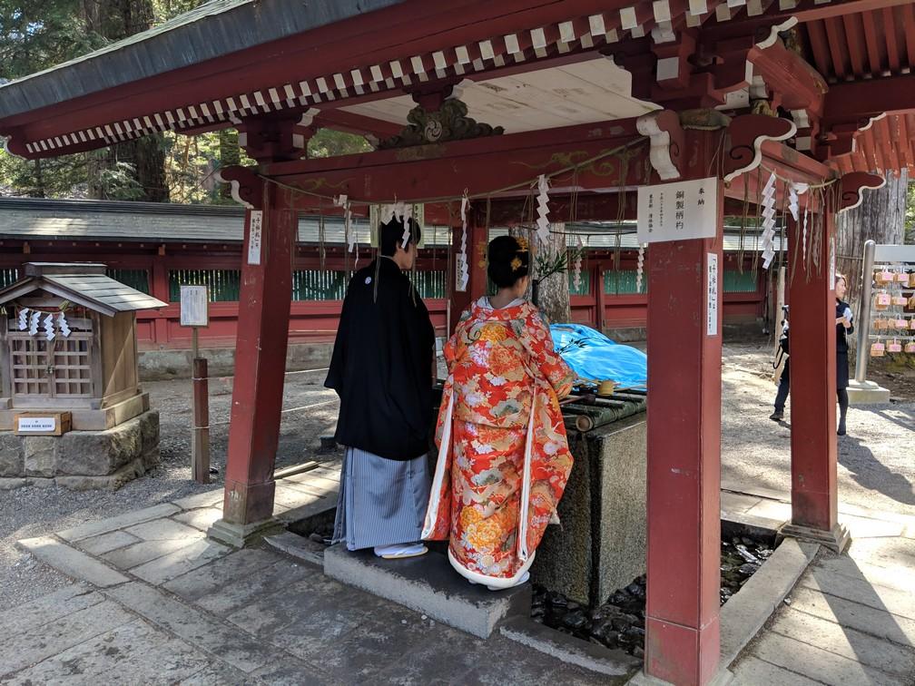 Couple de Japonais en tenue traditionnelle se lave les mains dans la petite fontaine de la zone de prière au sanctuaire Futurasan