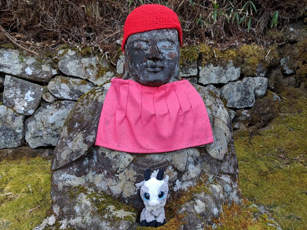 Biquette posée sur une statuette de Bouddha Jizô à Nikko