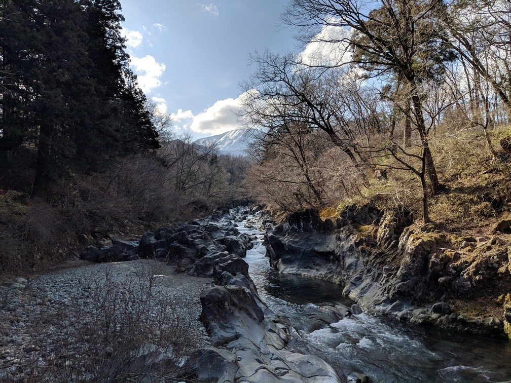 Rivière serpentant entre de gros rochers, une montagne enneigée au fond