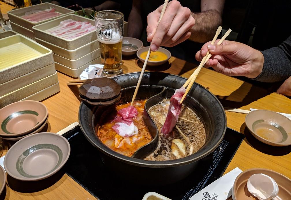 De la viande crue est plongée avec des baguettes dans de l'huile bouillante
