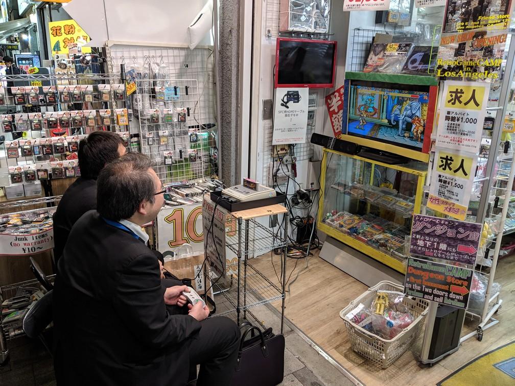 Deux salary men d'âge mûr s'affrontent devant une boutique de retro gaming