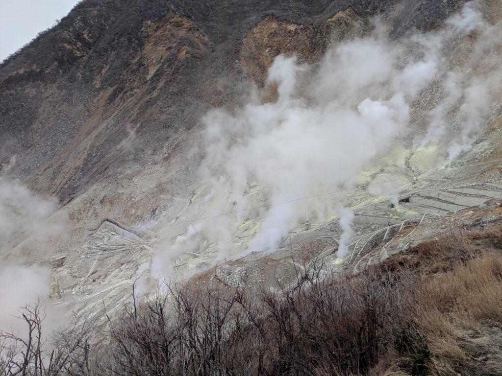 Des fumerolles s'échappent de l'exploitation de souffre dont la terre est jaune