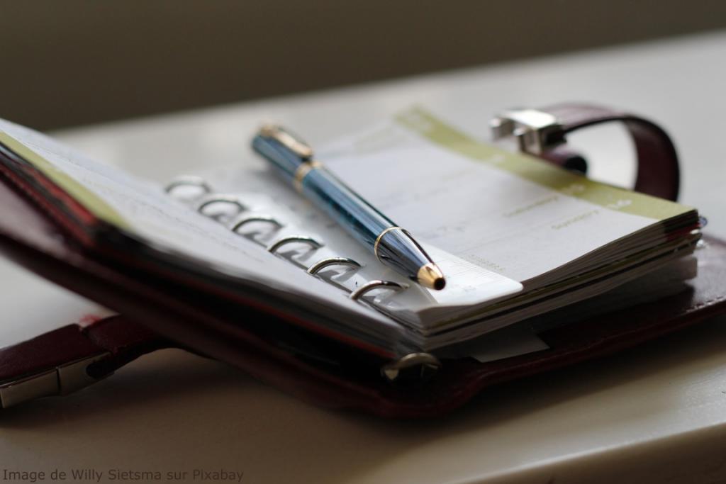 Un stylo est posé sur un agenda ouvert