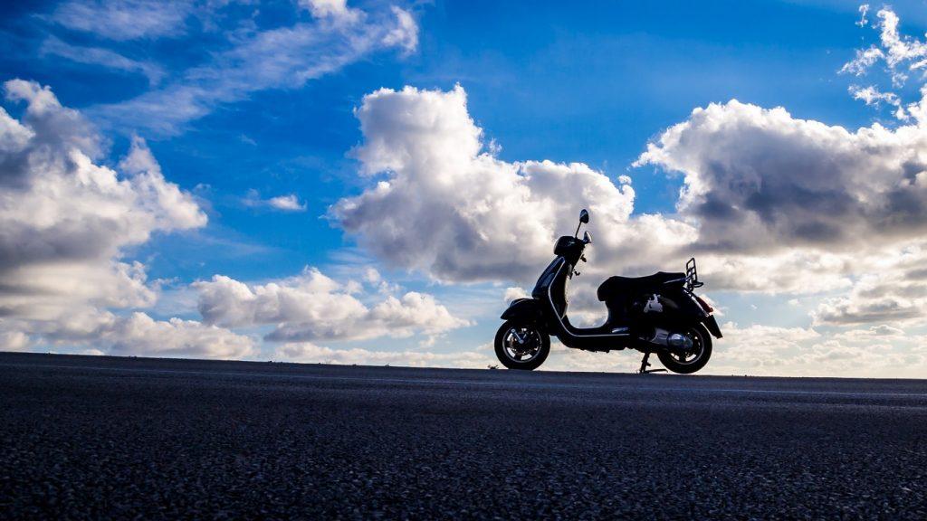 Un scooter à contre jour avec des nuages et un ciel bleu dans le fond