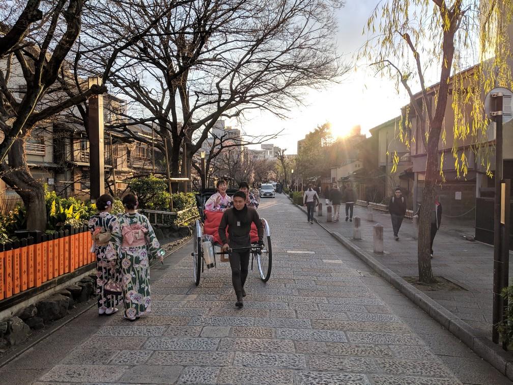 Des Japonaises en kimono croisent d'autres Japonaises dans un pousse-pousse