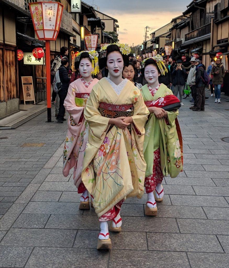 Trois Geishas marchent dans la rue, toute apprêtées