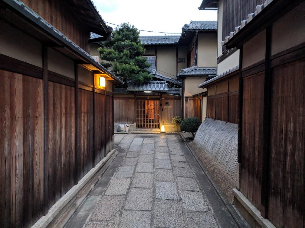 Une ruelle de pavé avec des murs en bois de chaque côté, des lanternes allumées car la nuit commence à tomber