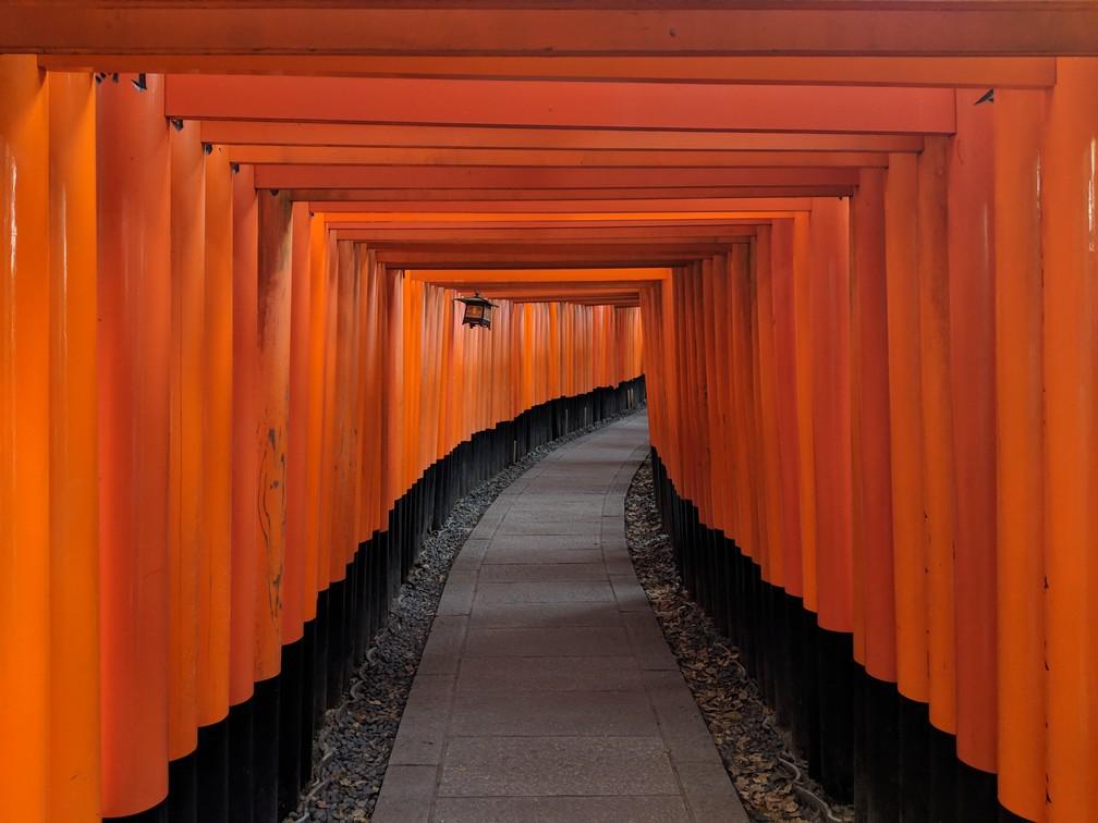 Une longue succession de portes rouges encadrent un petit chemin qui tourne
