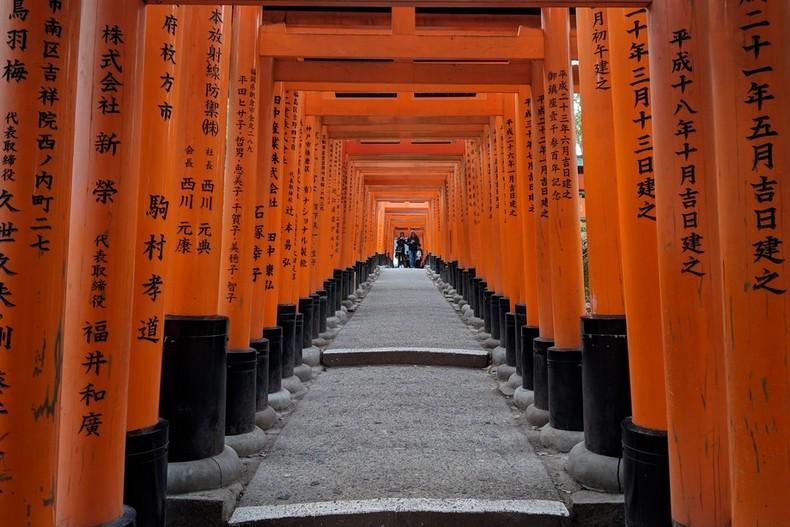 Des toris rouges entourent une petite montée, des inscriptions figurent sur les poteaux