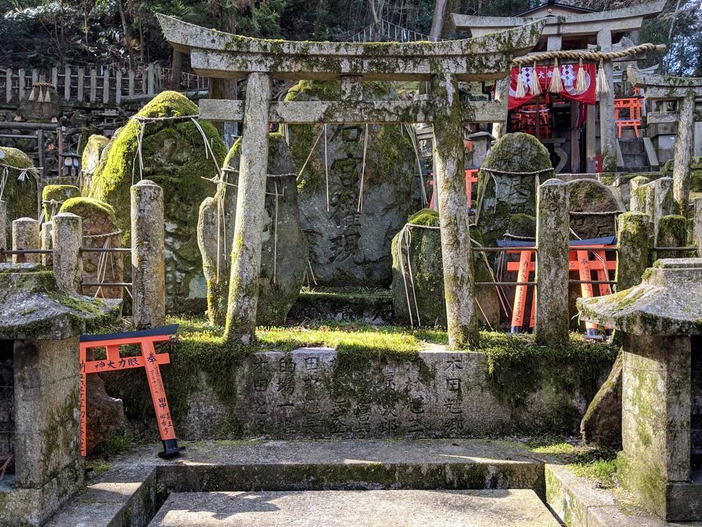 Des petites toris sont posées sur des tombes couvertes de mousse