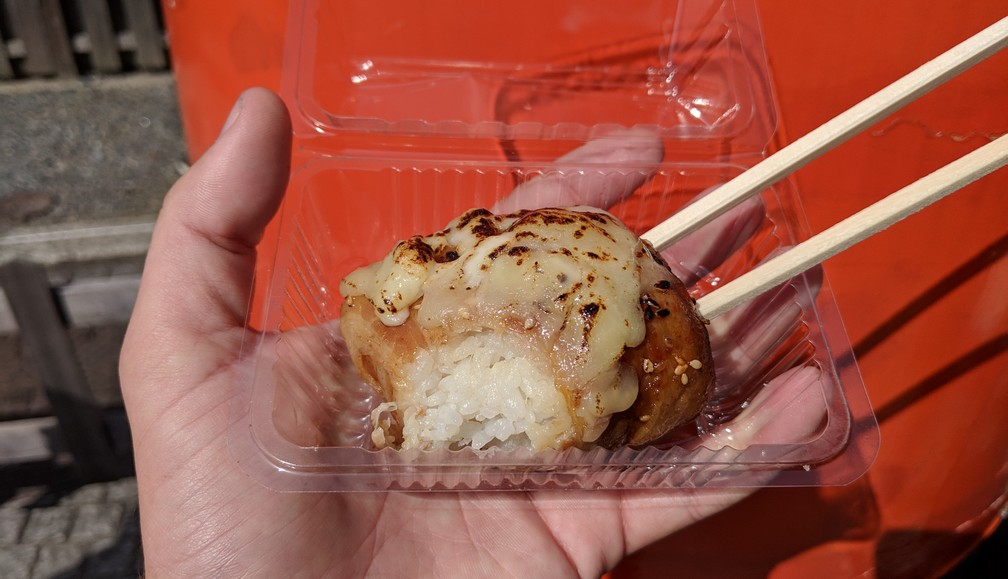 Une boule de riz entourée de viande partiellement mangée et tenue par des baguettes