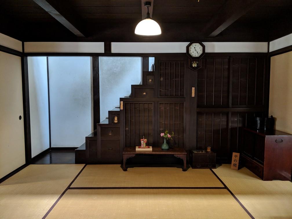 Un escalier en bois avec pleins de tiroirs montent à l'étage