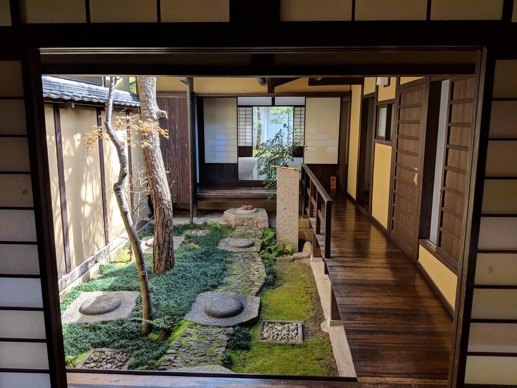 Un petit patio révèle un jardin intérieur à l'intérieur de la maison traditionnelle en bois