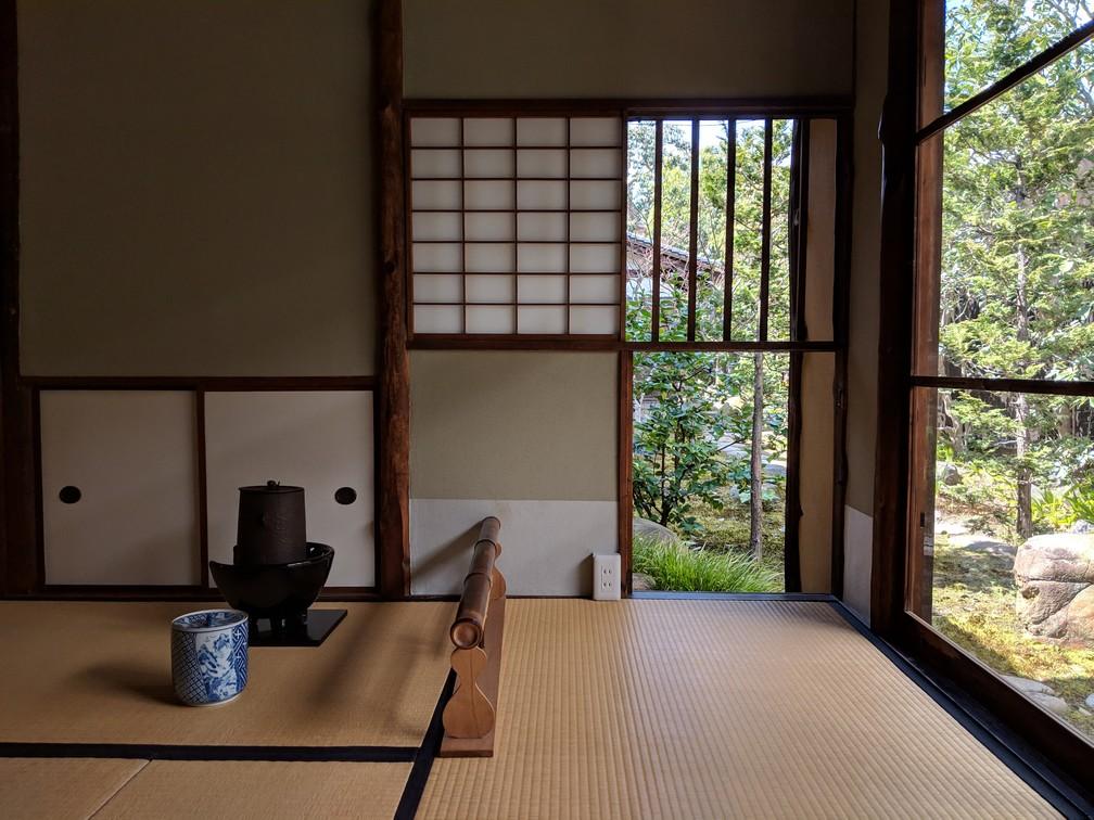 Un service à thé est posé par terre sur un tatamis dans une pièce avec des fenêtres sur le jardin
