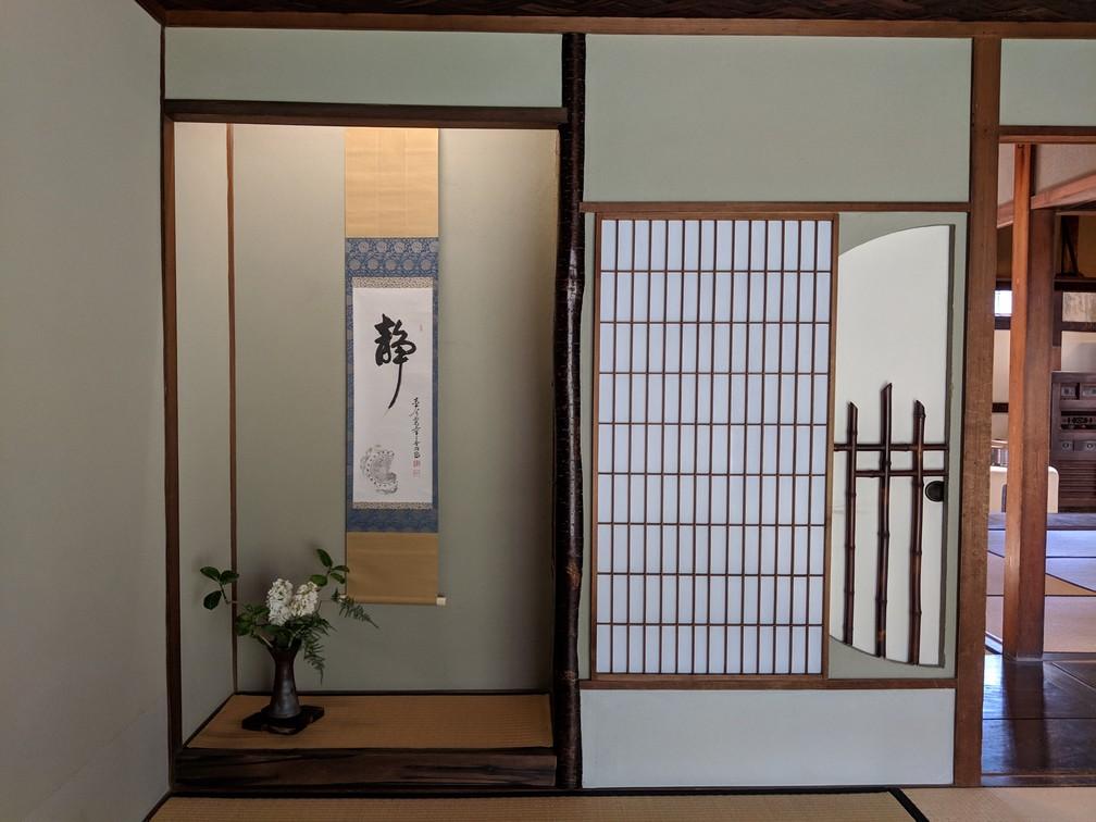 Une petite alcove avec un pot de fleur et une banderole avec un symbole japonais