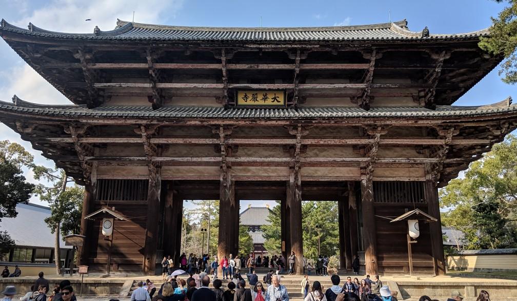 Une immense porte en bois avec deux toits superposés