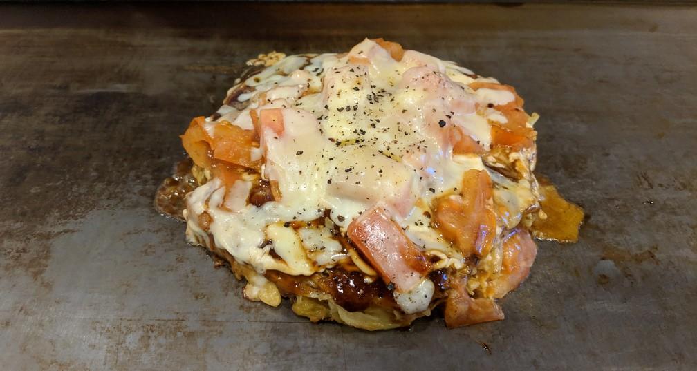 Une grosse omelette avec des tomates et du fromage
