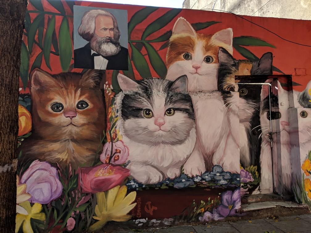Une fresque représente des chatons avec un portrait de Karl Marx au dessus