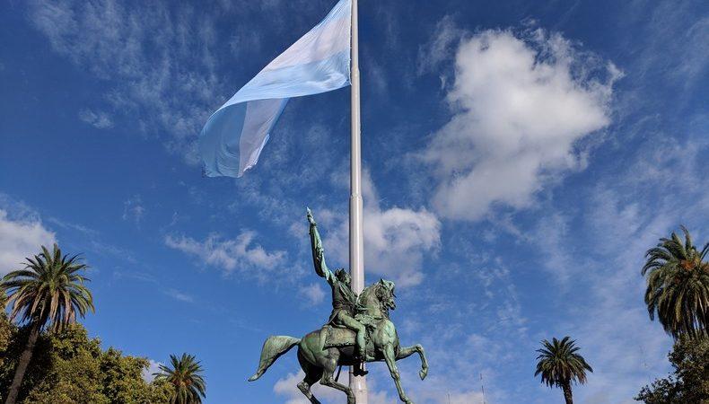 Une statue d'un cavalier devant le drapeau argentin flottant