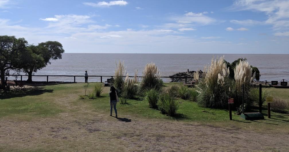 Salomé marche vers le bord du parc avec l'océan derrière