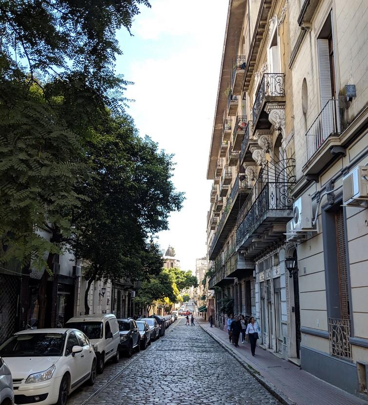 Un batiment haussmanien dans une rue pavée bordée d'arbres