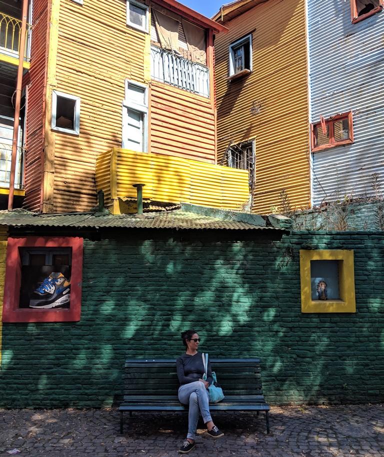 Salomé assise sur un banc devant des façades colorées de la Boca