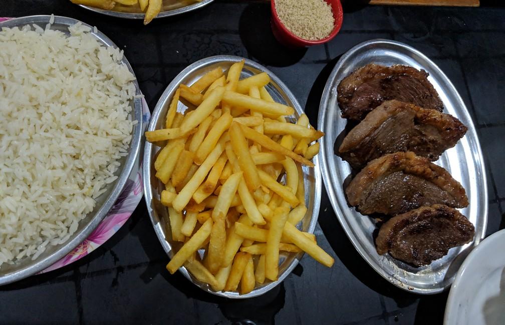 Une assiette de riz, une de frite et une de viande