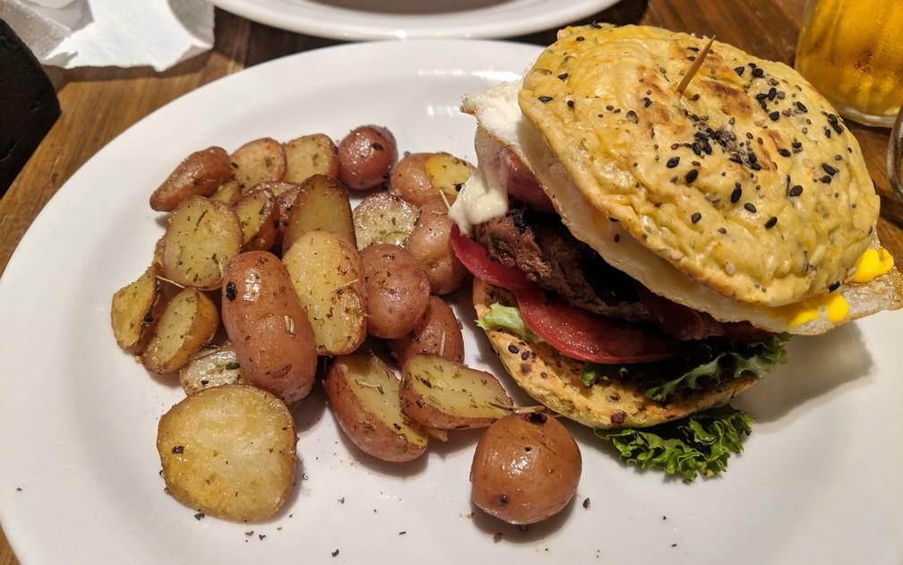 Un gros burger avec des petites patates en robe des champs