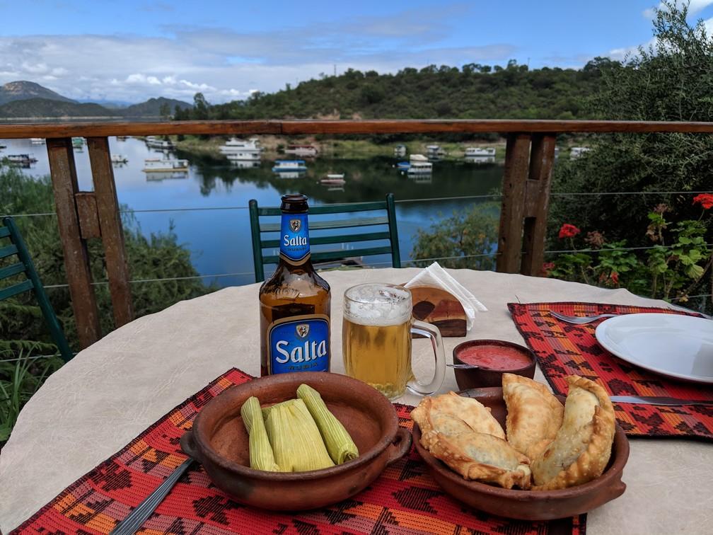 Une bouteille de bière et des empanadas posés sur une table devant le lac de Cabra Corral