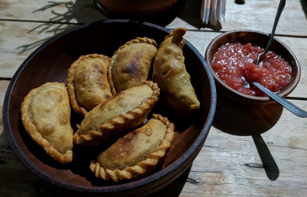 Un bol de six belles empanadas avec de la sauce à la tomate à côté chez El Rincon del Empanadas