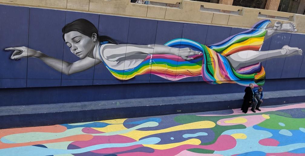 fresque murale représentant une jeune fille multicolore qui flotte à Santiago du Chili