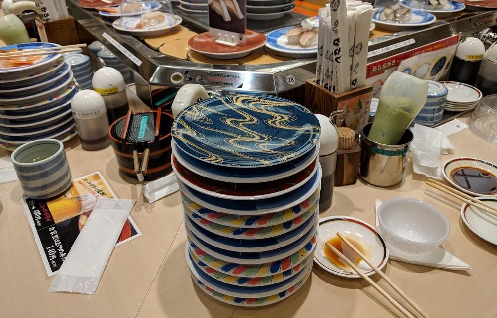 Plein de petites assiettes à sushi sont empilées, vides