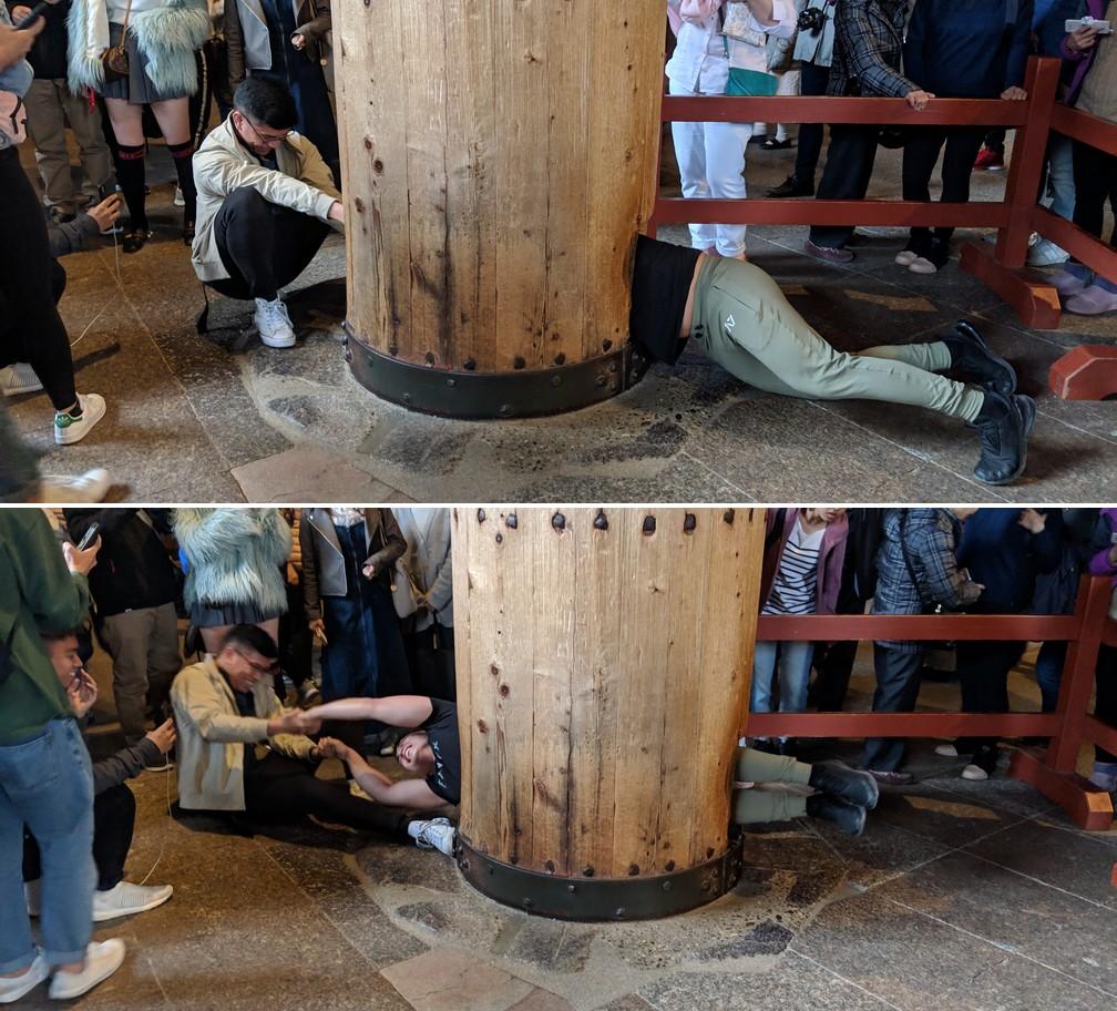 Un asiatique tire avec force un de ses amis à travers le pilier