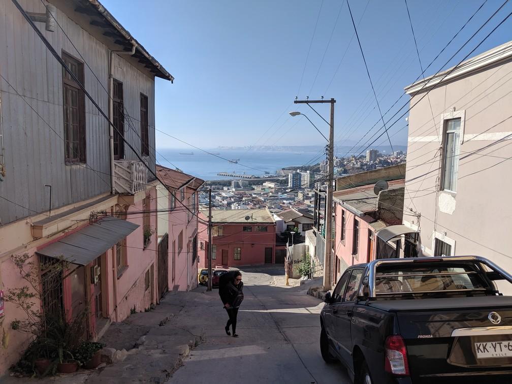Salomé avec son gros sac à dos monte une rue dans Valparaiso