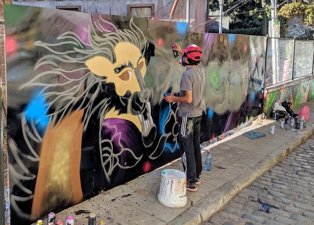 Un artiste de rue peint une fresque à la bombe à Valparaiso