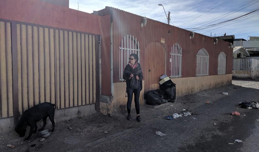 Salomé regarde inquiète un gros chien errant en train de manger des ordures dans une rue de Calama