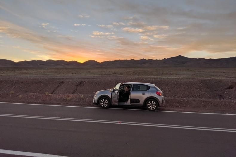 Voiture au bord de la route avec coucher de soleil à San Pedro de Atacama