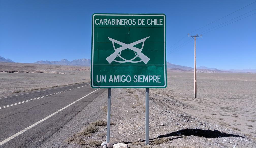 Un panneau sur le bord de la route au milieu du désert, afficant 'Carabineros de Chile, Un Amigo Siempre'