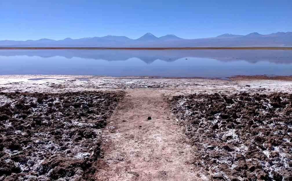 Chemin encrouté de sel devant la lagune Tebenquiche dans laquelle se réfléchissent des montagnes