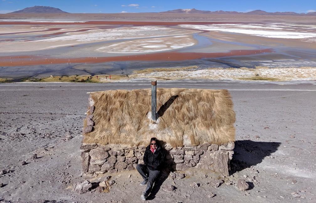 Salomé s'abrite derrière une petite maison en pierre devant la laguna colorada