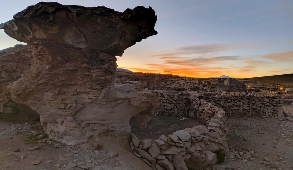 Un gros rocher avec le coucher de soleil derrière à Vila Mar