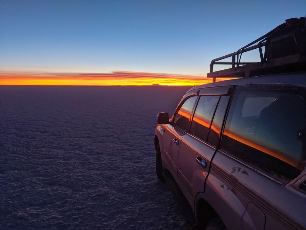 Le lever de soleil se réfléchit sur les vitres du 4x4 dans le salar d'Uyuni