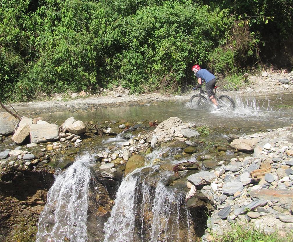 Matthieu traversant une rivière en VTT sur la Route de la Mort