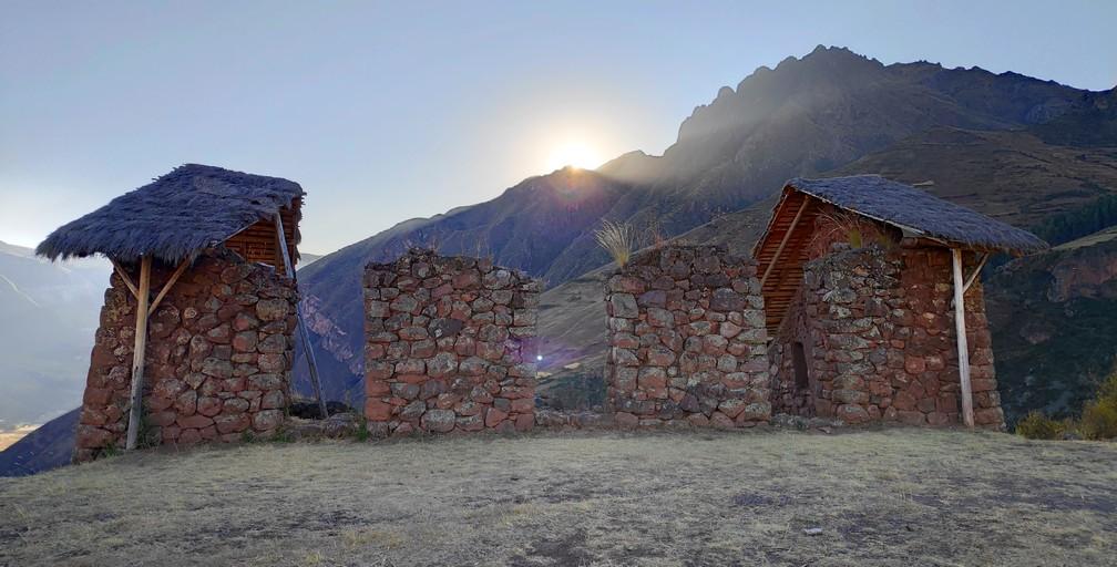 Coucher de soleil sur des maisons incas en ruine à Pisac