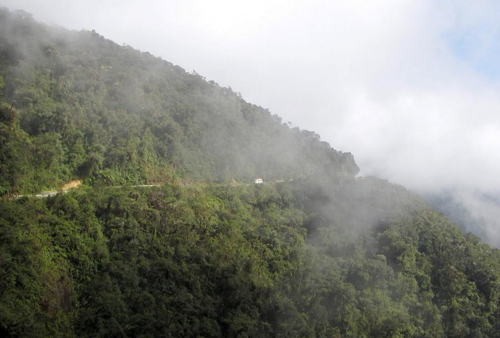 Un van circule sur la Route de la Mort vue au loin à flanc de colline près de La Paz