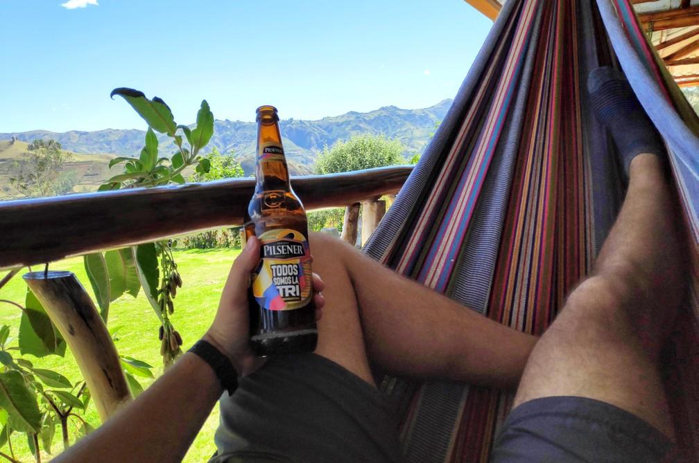 Sylvain déguste une bière dans un hamac avec vue sur les montagnes à Isinlivi